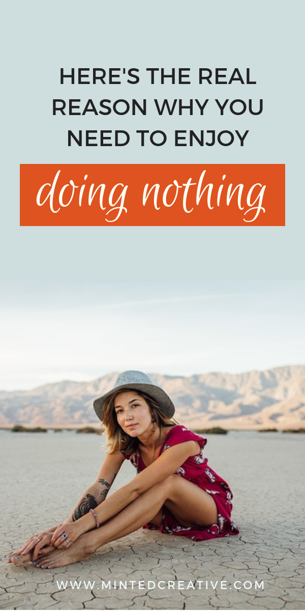 Girl in red dress and grey fedora sitting in the desert with text overlay -Here's The real Reason Why You Should Enjoy Doing Nothing