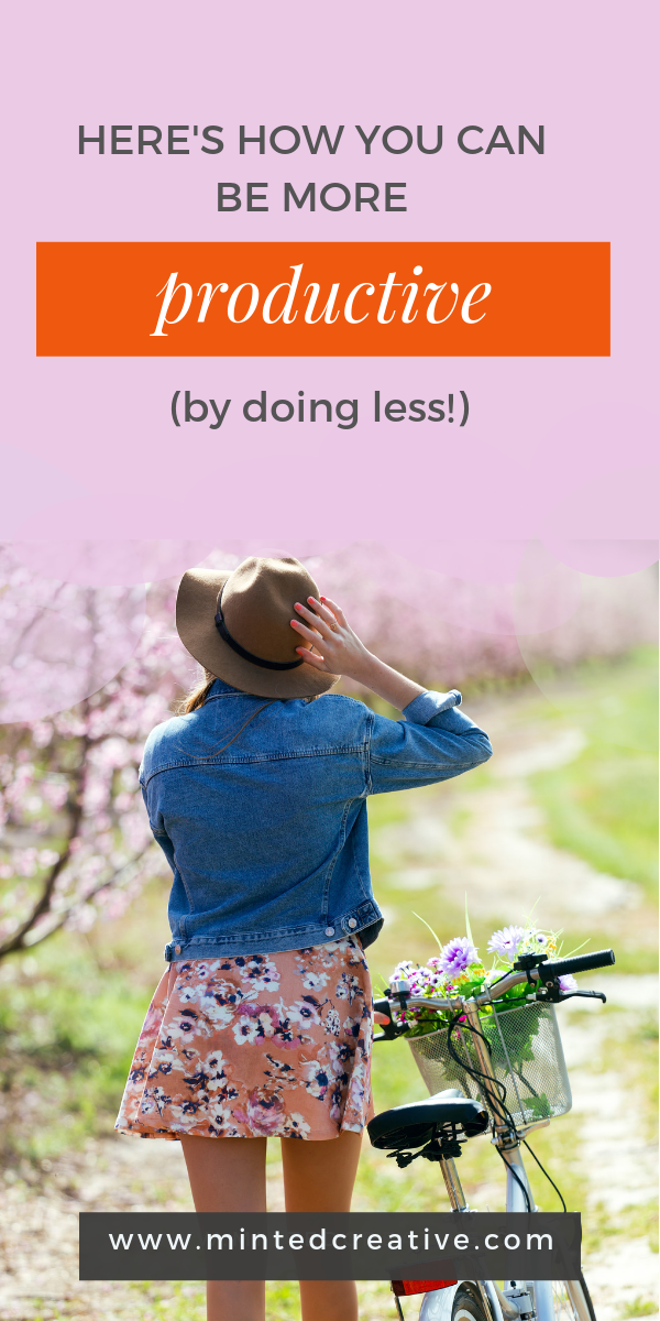 woman in hat and denim jacket walking with bicycle under cherry blossom trees with text overlay - how to be more productive by doing less.
