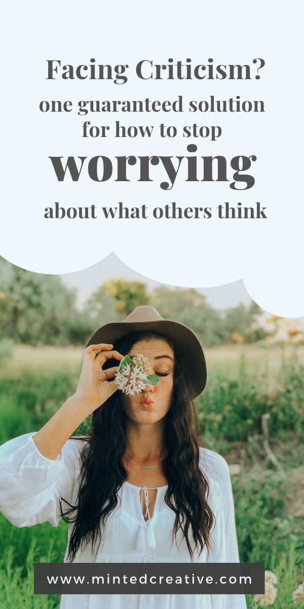 portrait of brunette woman with flower and text overlay - facing criticism? one guaranteed solution for how to stop worrying about what others think